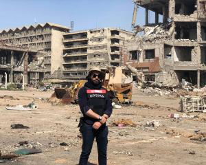 Mathew Zacharias' friend Mohammad stands in front of Ibn Sinaa Hospital, Mosul. Its ground floor...