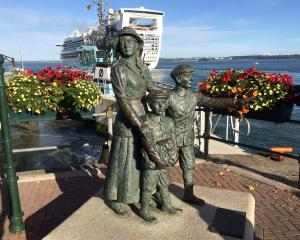 Diaspora memorial at the port of Cobh, Cork, with a modern cruise ship, Dawn Princess, leaving...