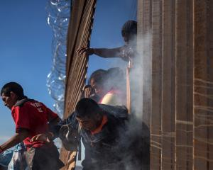 Migrants are hit by tear gas by US Customs and Border Protection after attempting to illegally...
