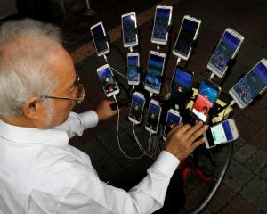 "Taiwanese Chen San-yuan, known as ""Pokemon grandpa"", plays the mobile game ""Pokemon Go"" by..."