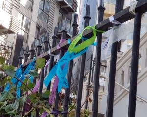 About 50 ribbons, signed with messages by victims and their supporters, were tied to the gates of...