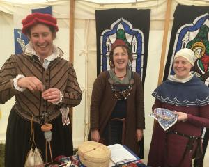 Simon Hindin aka Eleanora (left), spinning some wool, Anne-Marie Gilmore aka Melisande and Amy Wilson aka Adrienne, doing some embroidery, in the tent for the Barony of Southron Gaard, the Canterbury branch of the Society for Creative Anachronism, a middl