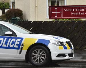 A police car sits outside Sacred Heart School in Dunedin after a pupil was grabbed by a man on a...