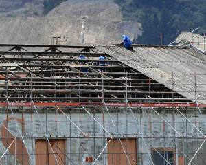 Contractors remove the roof of Port Otago sheds in Fryatt St. Photo: Stephen Jaquiery