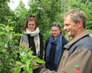 Waiau Area School pupils Holly Hammond (15, left) and Amanda Baldwin (18) chat with Hollandia Orchard manager Murray Booth.