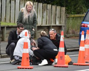 Members of the public assist a man after the incident in Halfway Bush. Photos: Gregor Richardson