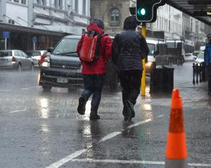 Heavy rain hits Stuart St as a front moves over Dunedin yesterday.