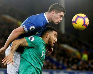 Everton defender Michael Keane (top) and Watford striker Troy Deeney compete for the ball in...