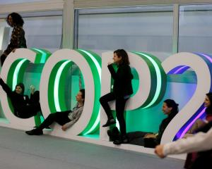People pose for a picture inside the venue of the COP24 UN Climate Change Conference 2018 in...