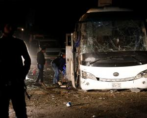 Police officers inspect a scene of a bus blast in Giza. Photo: Reuters