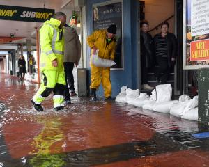 Dave Mitchell (right) and Tony Vaas sandbag shops in Mosgiel. Photo: Stephen Jaquiery