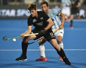 Black Sticks striker Marcus Child controls the ball as Argentina defender Pedro Ibarra looks on...