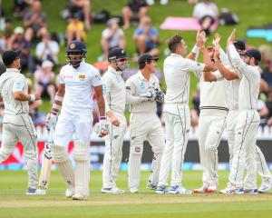 New Zealand's Tim Southee (4th R) celebrates with teammates after taking the wicket of Sri Lanka...