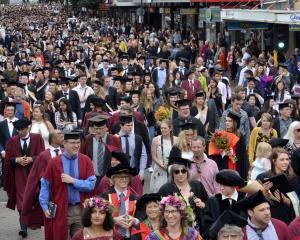 The latest University of Otago academic procession surges along George St, Dunedin, towards the...