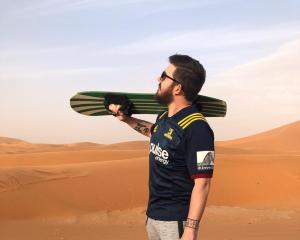 Billy Heron sports his Highlanders shirt while sandboarding. Photo: Matthew Wicks