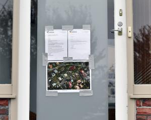An evacuation notice on the door of a Motu St, St Clair property. Photo: Peter McIntosh