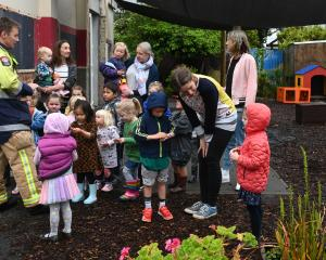 St Kilda firefighter Mark Fisher hands out stickers to children at St Clair Kindergarten after...