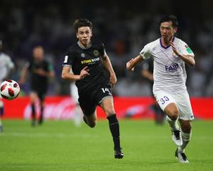 Jack-Henry Sinclair of Team Wellington and Tsukasa Shiotani of Al Ain chase the ball in their...