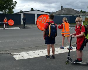Silverstream School pupil Luke McHale (8) prepares to cross Green St in Mosgiel on his scooter...