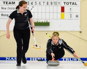 New Zealand women's skip Bridget Becker delivers her stone while team mate Jessica Smith looks on...