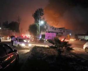 People react at the scene where a ruptured fuel pipeline exploded, in the municipality of...