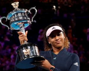 Naomi Osaka poses with the trophy after her victory in the Australian Open final. Photo: Reuters