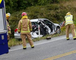 Balclutha fire officers sweep State Highway 1 clear of glass after a crash just north of the town...