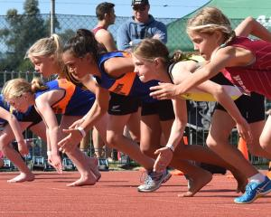 Girls in the grade 9 100m take off from the start line at the Colgate Games at the Caledonian...