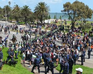 Police stand between the rival groups during their rallies in Melbourne on Saturday. Photo: Getty