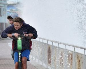 Two boys rider a Lime e-scooter at St Clair as waves crash against the Esplanade wall. Photo: Peter McIntosh