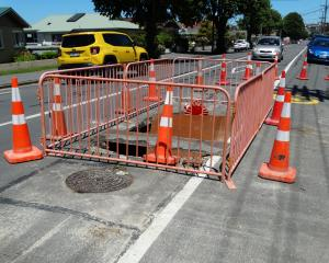 Motorists negotiate a fenced-off sinkhole in Reed St that opened up in late December. Work to...