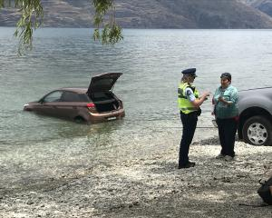 An American tourist talks to police after her rental car rolled into Lake Wakatipu yesterday....