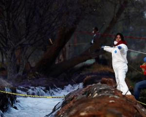 Forensic technicians work at the site where a fuel pipeline ruptured by suspected oil thieves...