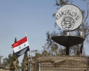 A Syrian national flag flutters next to the Islamic State's slogan at a roundabout where...