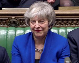 British Prime Minister Theresa May reacts as Jeremy Corbyn speaks, after she won a confidence...