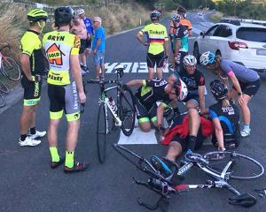 Bunch riders support one another after the crash on State Highway 30. Photo: NZME