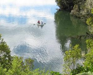 Rowers paddle near one of New Zealand's most remote holiday homes now up for sale on Stewart...