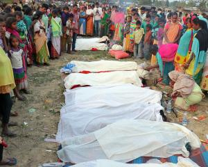 People stand next to the bodies of tea plantation workers, who died after consuming bootleg...