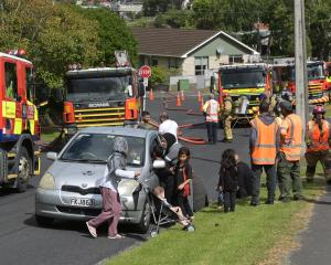 Members of Dunedin's Syrian community watch as firefighters battle a fire, yesterday afternoon,...