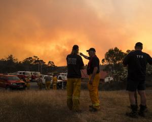 Fire fighters, medics and police plan fire control strategies for the evening near Minea in...