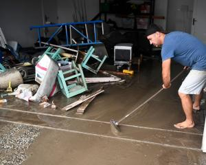 Townsville resident David Mitchell sweeps out his muddy garage after floodwaters receded in the...