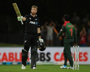 Martin Guptill of New Zealand celebrates scoring 100 runs during game one of the ODI series...