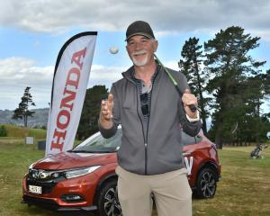Golfer Giorgio Accorsi with the ball and club he used yesterday to win a new car which is behind...