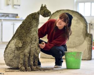 Jenny Hjertquist puts the finishing touches on one of her mythological dogs that will feature in...