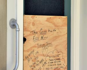 Messages and a bible reading were scrawled on a piece of plywood covering the smashed door to the...