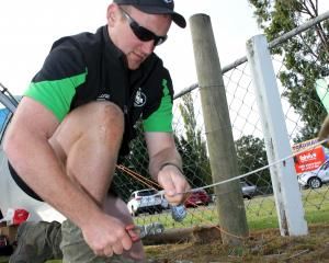 Wyndham sheep and beef farmer Matt McRae works on a fencing challenge at the regional final of...