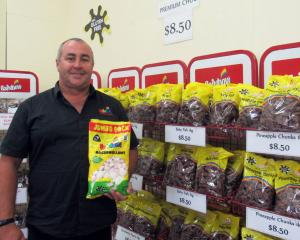 Rainbow Confectionery general manager Brent Baillie stands in front of bags filled with classic...