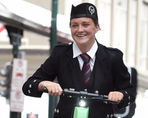 Briana Dent, of Balclutha Pipe Band, rides a Lime scooter during the 2019 RNZPBA Otago Centre...
