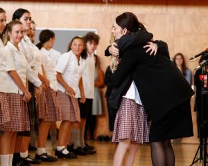 Prime Minister Jacinda Ardern hugs a pupil during her visit to Cashmere High School, in...