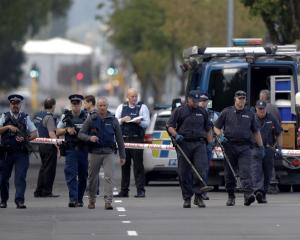 Police officers search the area near the Masjid Al Noor mosque in Christchurch following the...